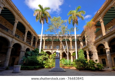 The ancient spanish government palace in Old Havana with a statue of Christopher Columbus and exuberant tropical vegetation - stock photo
