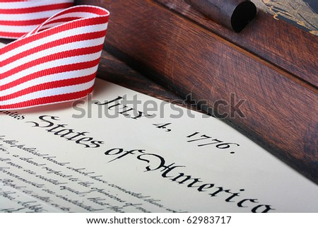 The ancient text of the declaration on independence of the United States of America with a casket and a feather for the write.