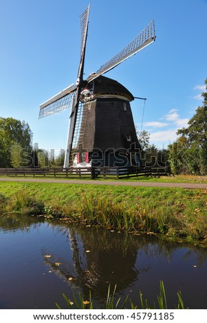The ancient windmill is reflected in water of a small pond. Clear autumn day in the Netherlands