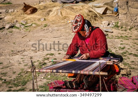 THE ANDES, PERU - JUNE 1, 2012: Quechua woman working in a village in the mountains of The Andes over Ollantaytambo, Peru - stock photo