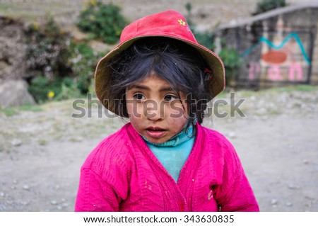 THE ANDES, PERU - MAY 30, 2012: Quechua girl staring in a village in the mountains of The Andes over Ollantaytambo, Peru - stock photo