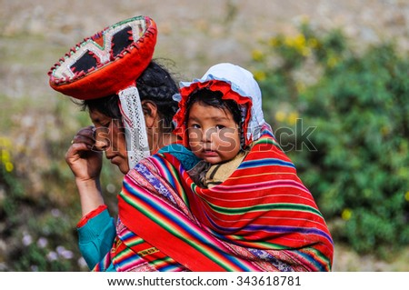THE ANDES, PERU - MAY 30, 2012: Quechua woman and baby in a village in the mountains of The Andes over Ollantaytambo, Peru - stock photo