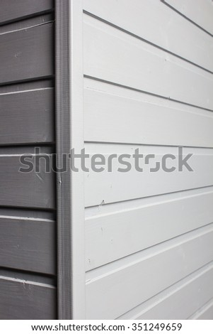 the angle of the wall decorated with wooden a siding and painted of gray color