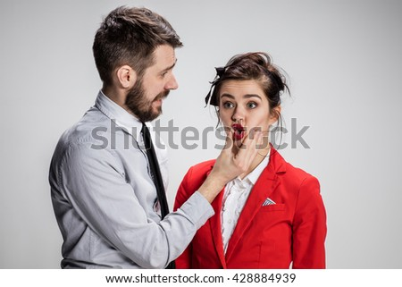 The angry business man and woman conflicting on a gray background