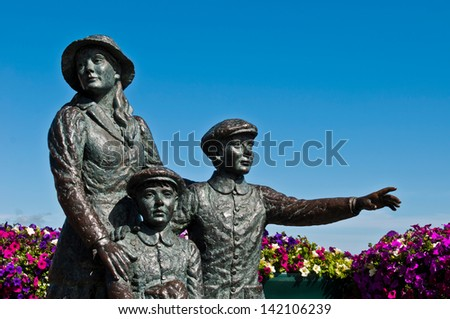 The Annie Moore Memorial, statue of Annie Moore and her two Brothers in Cobh, Ireland (Annie was the first immigrant to the United States to pass through the Ellis Island facility in New York Harbor) - stock photo