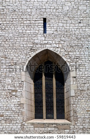 The antique window in old stone wall - stock photo