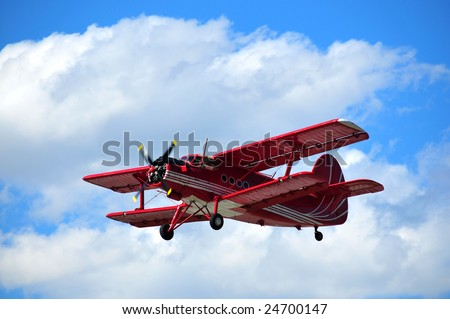 The antonov An-2 bi-plane colored red, with a swiss flag design flying in the swiss alps - stock photo