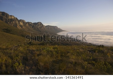 The 12 Apostles of Table Mountain tower above Camps Bay and Bakoven - stock photo