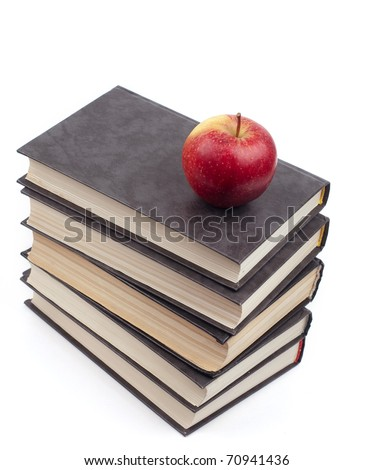 The apple lies on a pile of books - stock photo