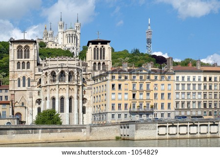 The apse of the Saint Jean cathedral, next to the Saone river, is dominated by the Fourviere basilica. (Lyon – France) - stock photo