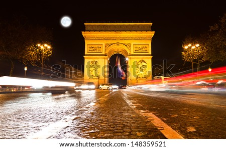 The Arc de Triomphe in Paris illuminated at night.   - stock photo