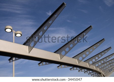 The arc of a modern steel archway stands against a clear blue sky. - stock photo