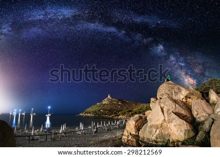 The arc of milky way over a beach with a lonely man on rocks admiring it. - stock photo