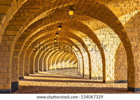 The arched stone colonnade with suspended lanterns - stock photo