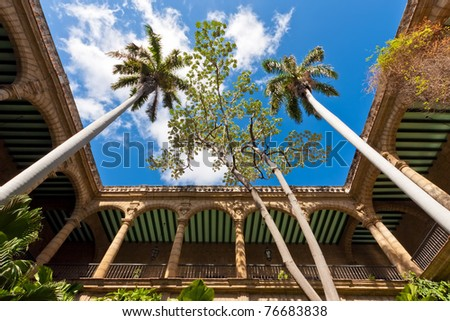 The arches and columns of the ancient spanish government palace in Old Havana with an exuberant tropical vegetation - stock photo