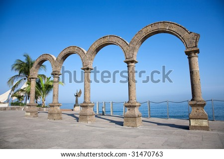 The arches of Puerto Vallarta Mexico over looking the crystal blue water with the Angel in background - stock photo