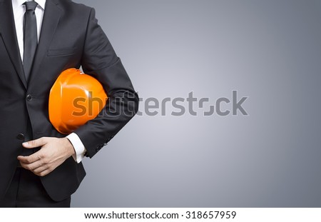the architect  hold  a helmet in his hand, on the gray  background. - stock photo