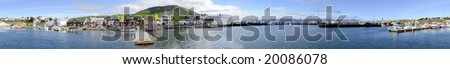 The arctic harbor of Husavik along the Skjalfandi bay, Iceland, with a colorful array of fishing ships, from where tourists are taken on whale watching trips - stock photo