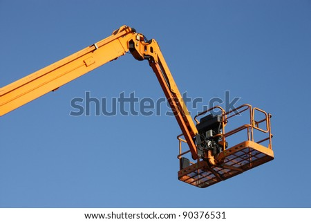 The Arm and Platform of a Yellow Cherry Picker. - stock photo