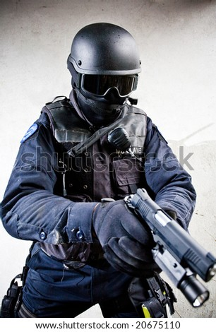 The armed soldier in a camouflage costs in alertness on a gray background - stock photo