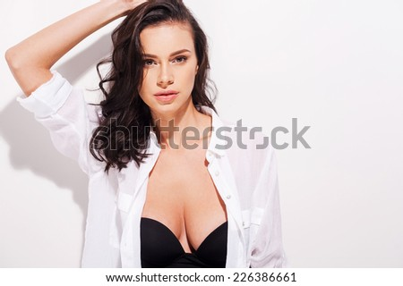 The art of seduction. Beautiful young woman in unbuttoned shirt holding hand in hair and looking at camera while standing against white background   - stock photo