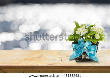 the artificial jasmine flower in the pot at the wooden table on abstract pastel blurred background - stock photo