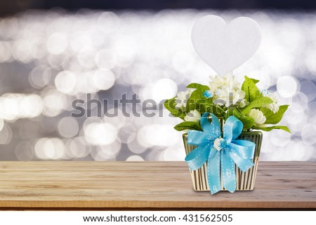 the artificial jasmine flower in the pot at the wooden table on abstract pastel blurred background