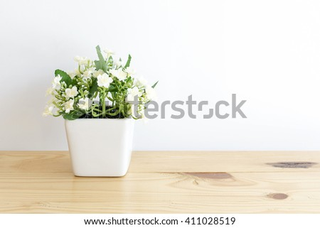 the artificial jasmine flower in the pot at the wooden table with the white wall background.The hand made jasmine flower in the white pot with the white background.The beautiful jasmine in the house. - stock photo