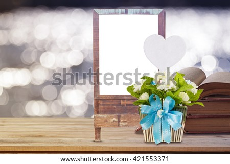 the artificial jasmine flowers in the pot at the wooden table on abstract pastel blurred background