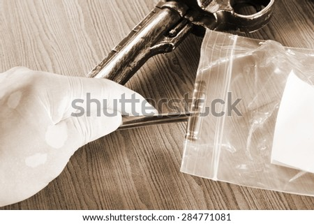 The artificial vintage plastic toy gun beside forceps in action of holding bullet on sepia tone represent crime science investigation instrument concept related idea - stock photo