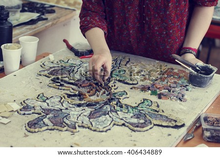 The artist collects mosaic. Female hands closeup collect mosaic of colored stones . - stock photo