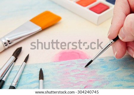 The artist does a picture on watercolor page. - stock photo