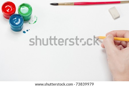 The artist does a sketch by a pencil on blank watercolor page. On a page paint, brush, rubber. - stock photo