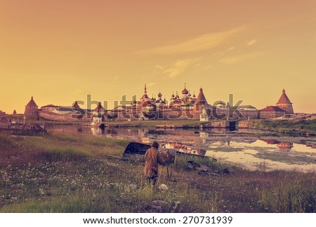 The artist paints a picture of nature at sunset with the castle in the background. Solovetsky monastery. toning effect - stock photo
