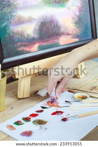 The artist paints a picture of the landscape using oily paints mounted on an easel. Selective focus - stock photo