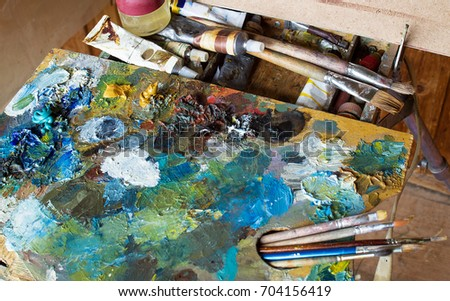 The artist's palette covered with colors, with tassels, lying on the sketchbook.