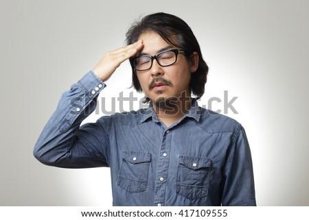 The asian man in blue denim shirt is feeling sick. - stock photo