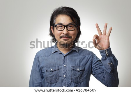 The asian man in blue denim shirt is showing okay sign - stock photo