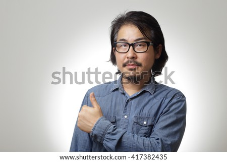 The asian man in blue denim shirt is showing thumb up.