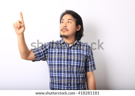 The asian man in the blue plaid shirt is pointing in the air. - stock photo