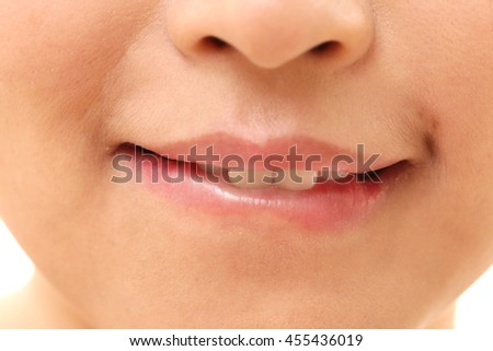 The Asian woman bite her lips.