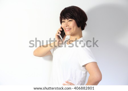 The Asian woman speaking at the mobile phone. - stock photo