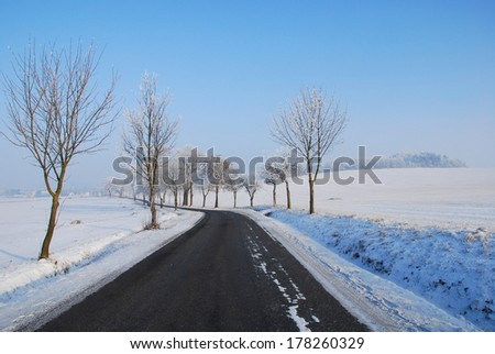 The asphalt road in a winter landscape - stock photo