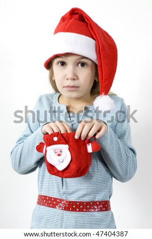 The astonished girl in red Santa`s hat with a Christmas gift
