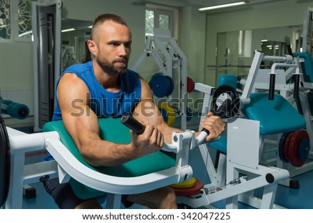 The athlete does bench biceps on the simulator in the gym. Hand muscle training on the simulator. Tense muscles of hands under load. Photos for sporting magazines, posters and websites. - stock photo