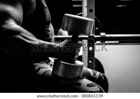 The athlete doing exercises for hands with dumbbells  - stock photo