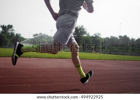 The athlete is running in the stadium.