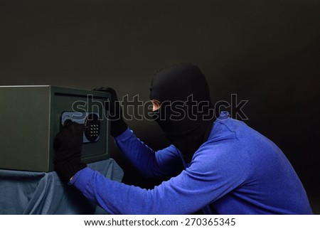 The attacker opens the safe on a black background - stock photo