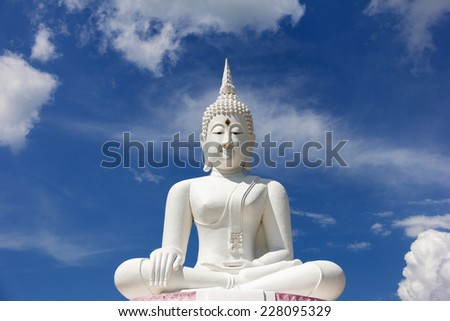 the attitude of meditation white buddha against blue sky - stock photo