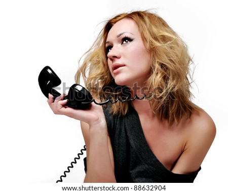 The attractive and sexual woman speaks by phone on a white background - stock photo